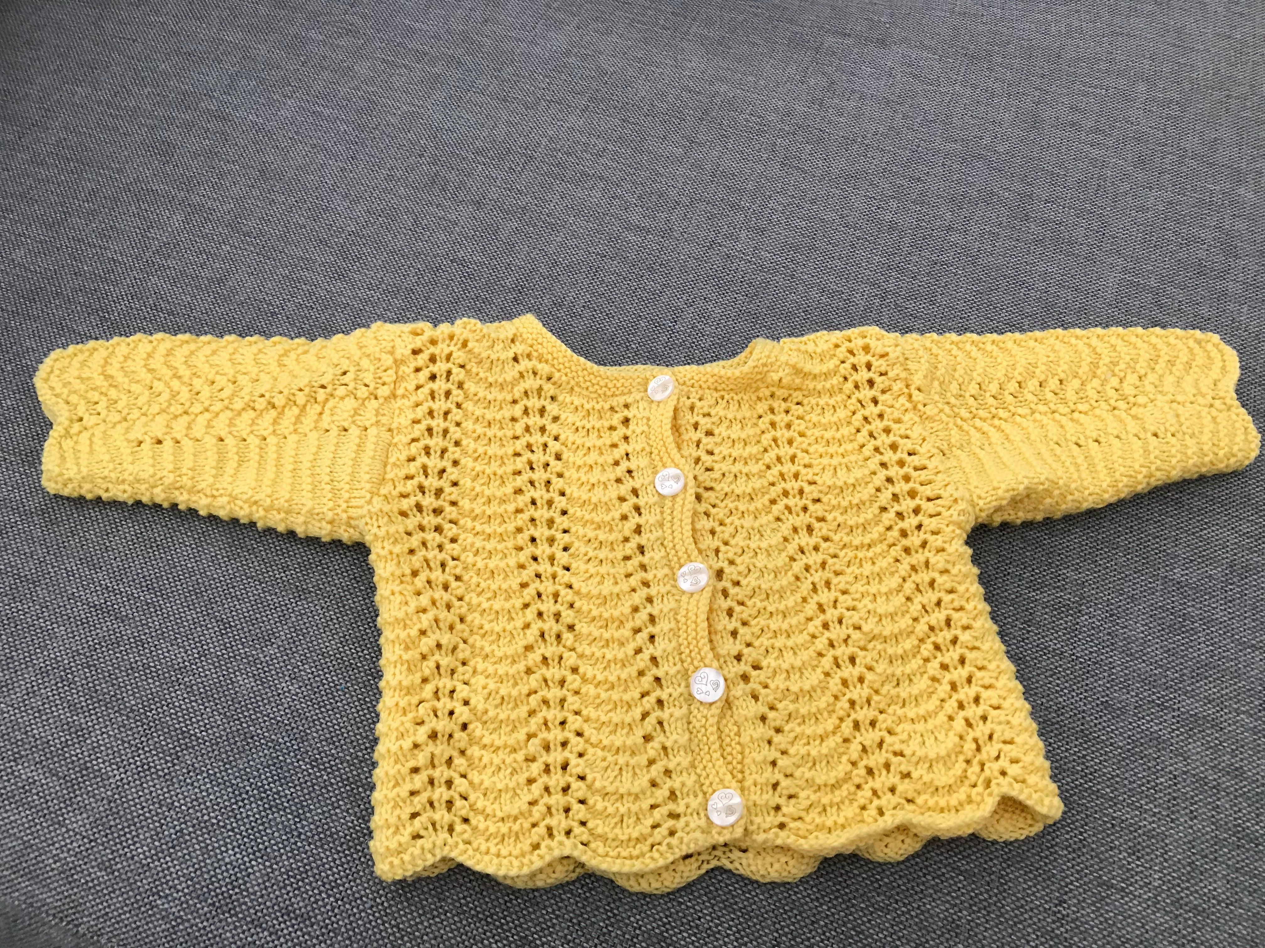 gul stickad tröja med knappar i mitten för att knäppa av/på. passar bebisar 0-3 månader