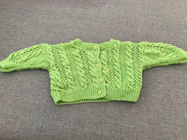 grön stickad kofta med gröna stjärnknappar som passar bebisar 0-3 månader