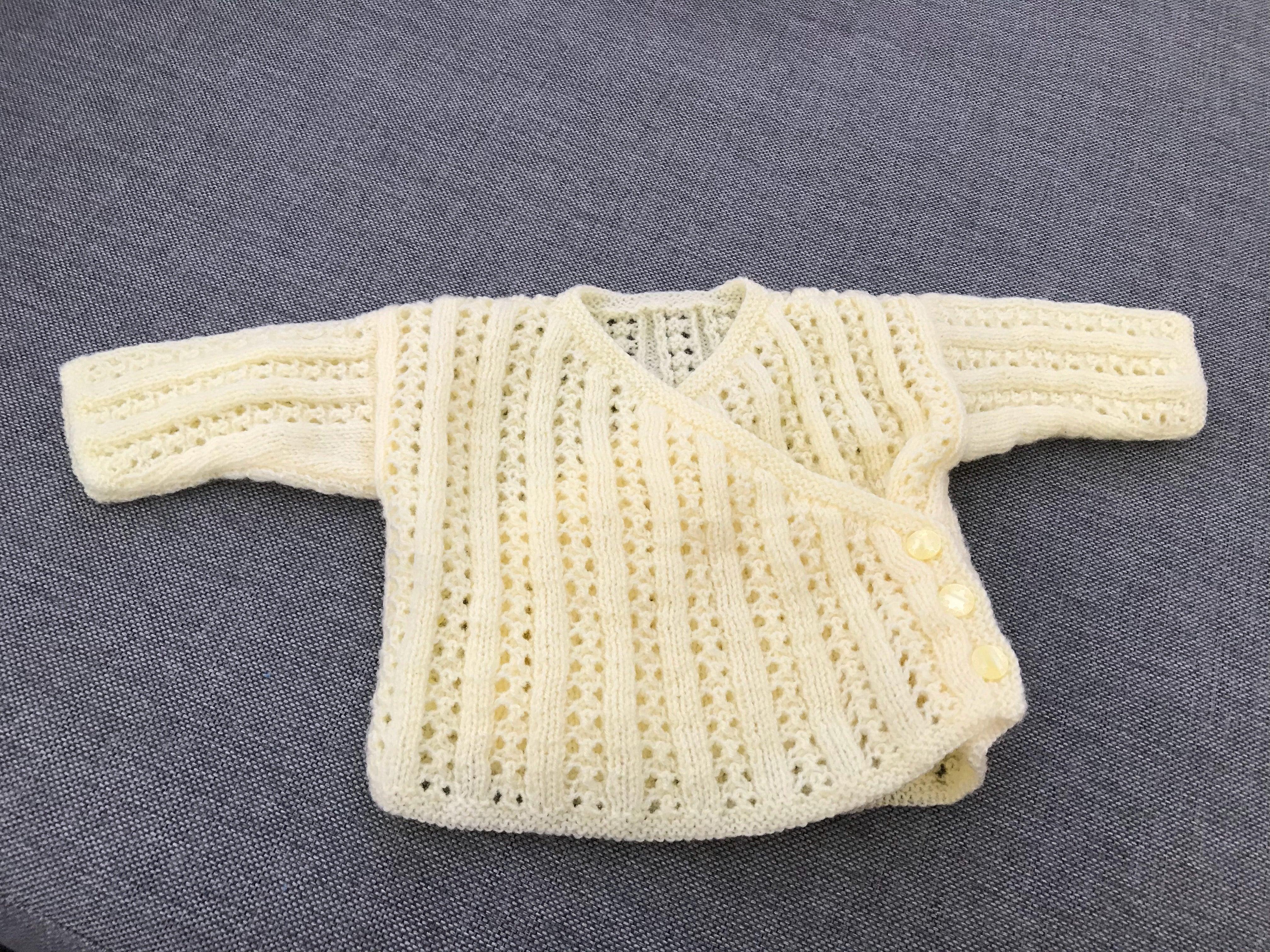 Ljusgul stickad omlottkofta med tre knappar vid sida, passar bebisar 0-3 månader