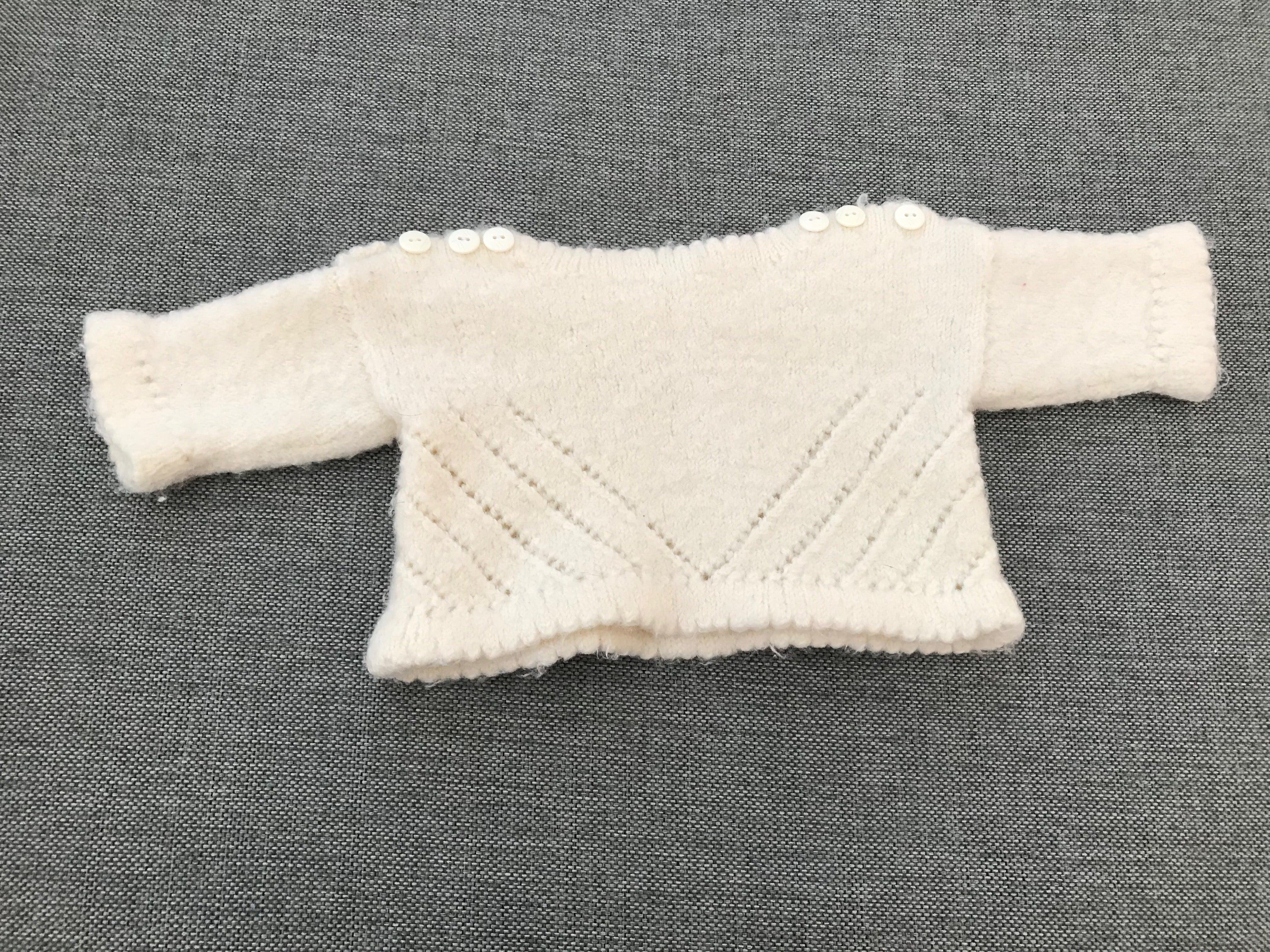 vit stickad tröja med 3 vita knappar på vardera axel, som passar bebisar 0-3 månader