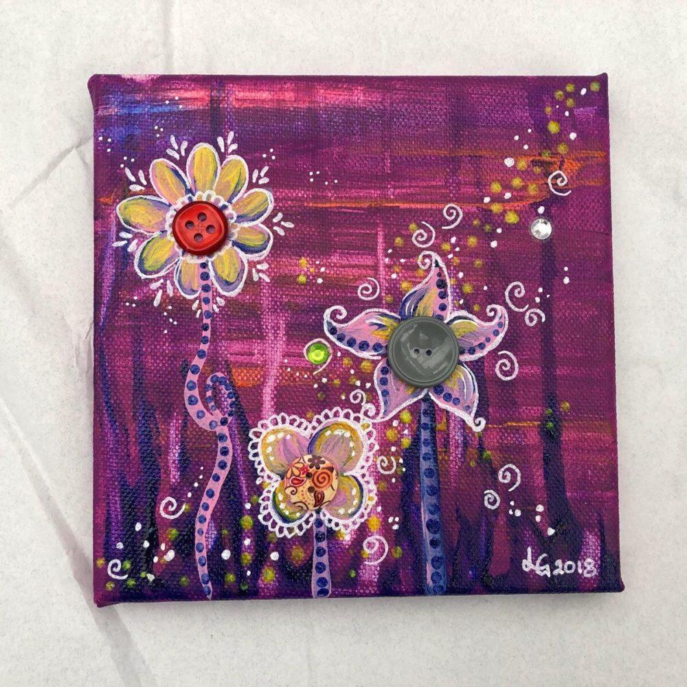 Konstnären Linda Gartman har skapat en canvas tavla med knappar, blommiga motiv i cerisefärgade toner.