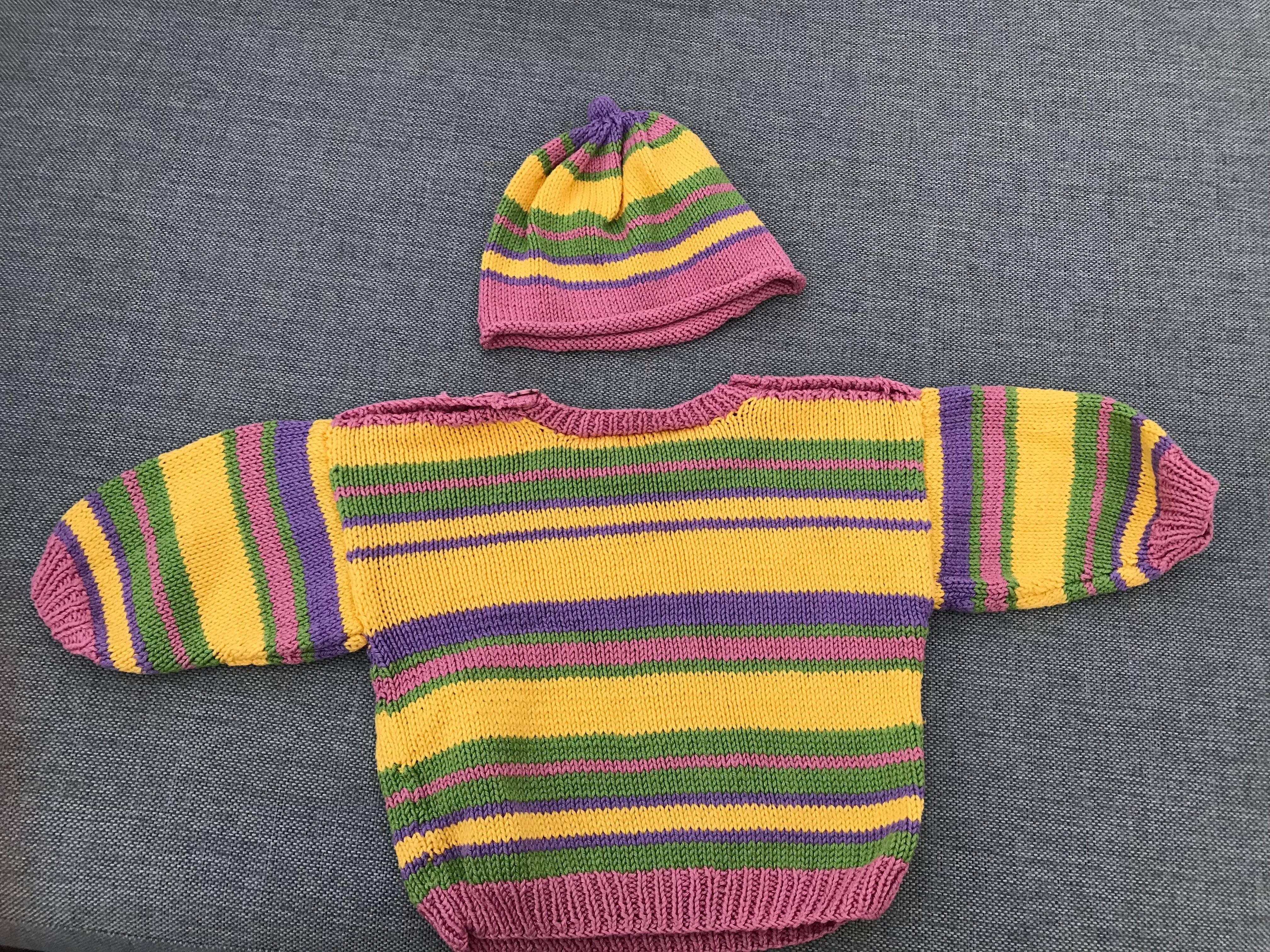 Vacker stickad tröja med ränder av lila, rosa, grönt och gult. Matchande mössa ingår.