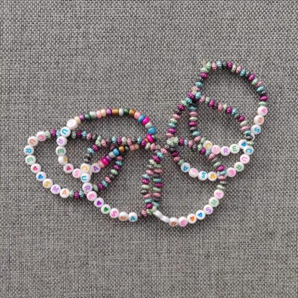 Armband med texten CURE SMA i regnbågens alla färger.