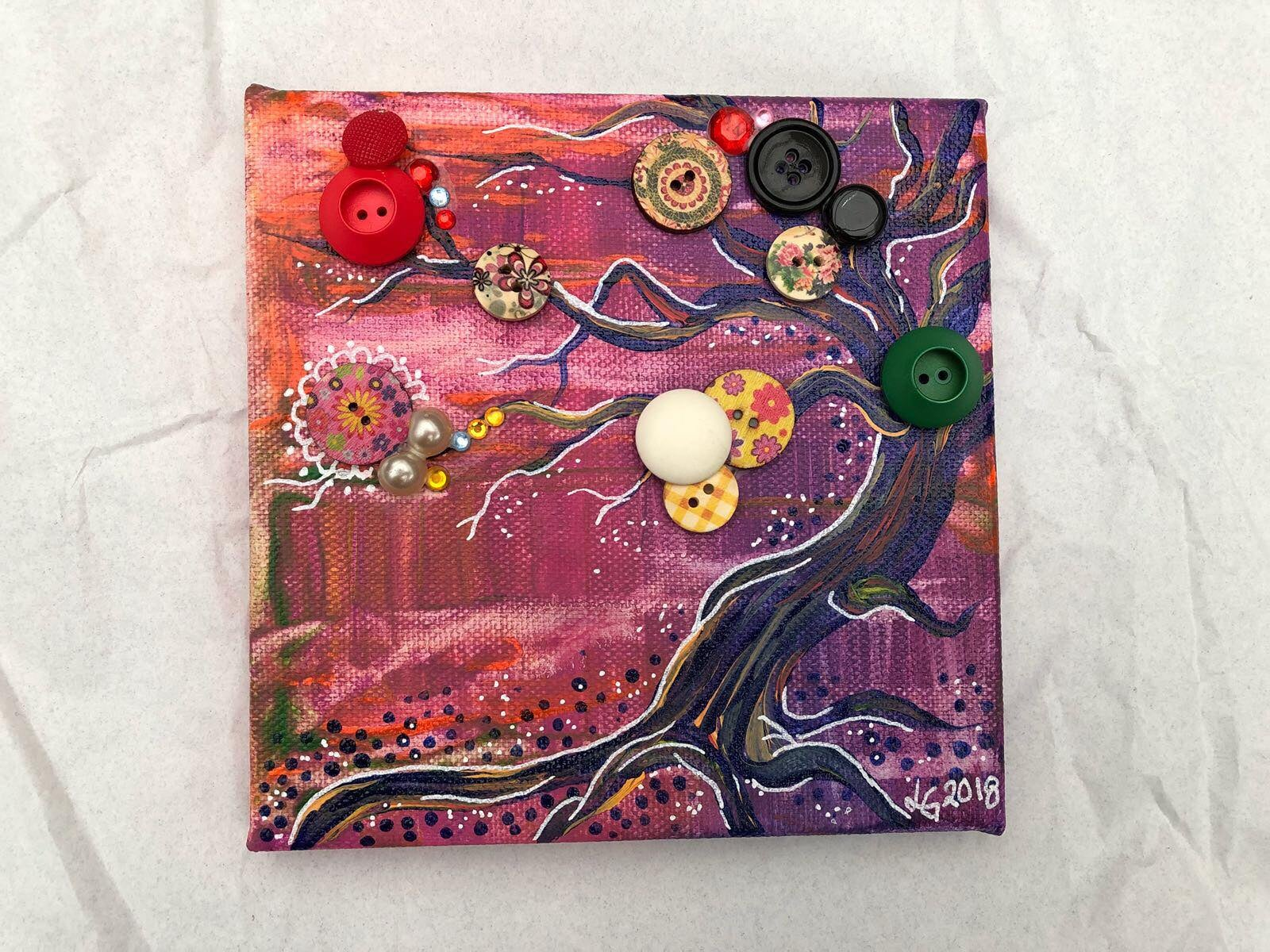 Konstnären Linda Gartman har skapat en canvas tavla med knappar på ett vackert stort träd. Färgerna är i grått och cerise toner.