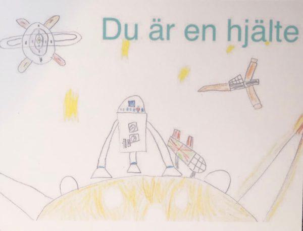 """Ett kort skapat av våra unga konstnärer, med texten """"Du är en hjälte"""". Motivet är en raketer och rymdfarkoster."""