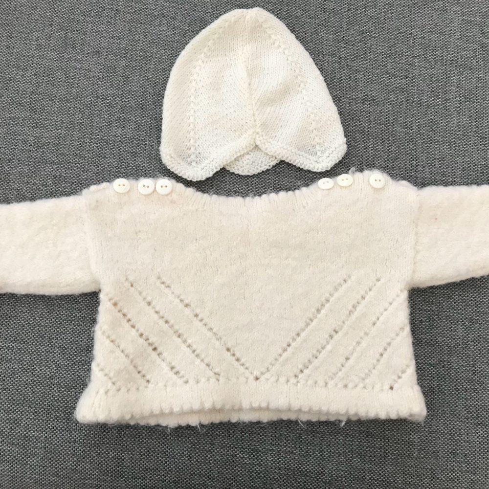 vit stickad tröja med 3 vita knappar på vardera axel, som passar bebisar 0-3 månader, matchande mössa ingår